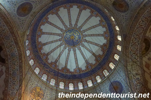 The beautiful tiled dome of the Blue Mosque, looking up from the floor.