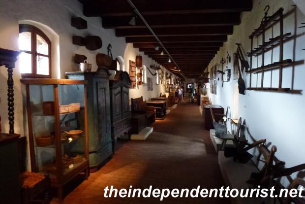 The elevated hall leading to the Latrine Tower, with many displays of old farm tools and home furnishings.