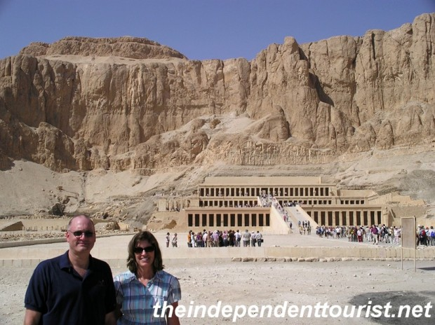 The Temple of Hatshepsut at the base of a dramtic limestone cliff.