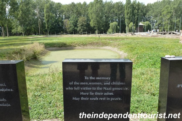A plaque noting the pond in the background, where the ashes of thousands were dumped from the crematoria.