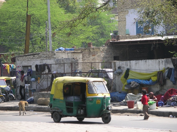 A street scene in Delhi, with an auto rickshaw passing street dwellers. Poverty is found everywhere.