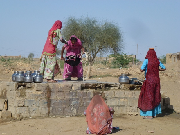 Women gathering water at a well in the desert - almost a biblical scene of life in the  desert.