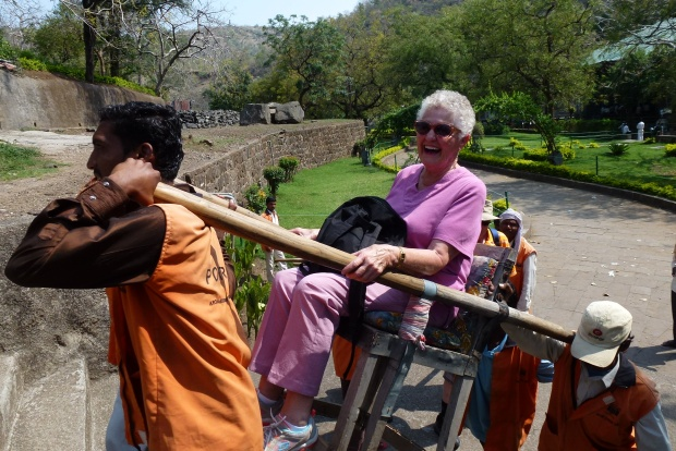 My mother-in-law getting a ride from porters up to the caves.