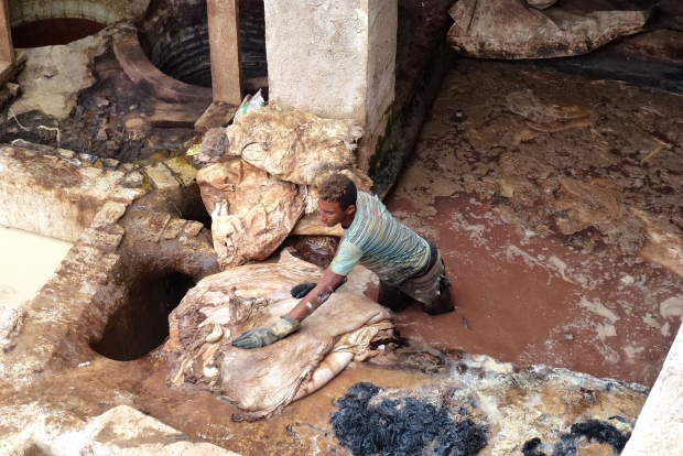A worker in the vats at Gueliz tannery. I am really glad I don't have his job!